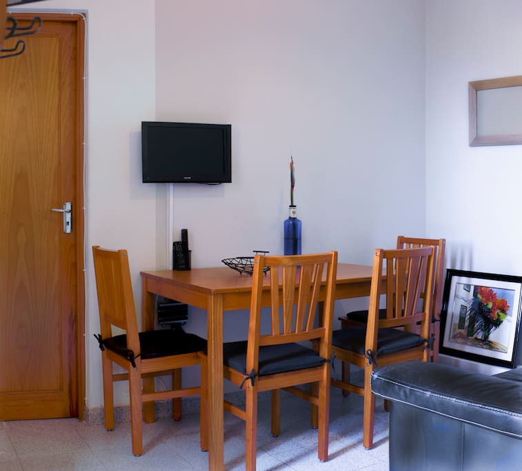A compact sitting room with sofa, TV (usb ready) and a table seating 4 persons