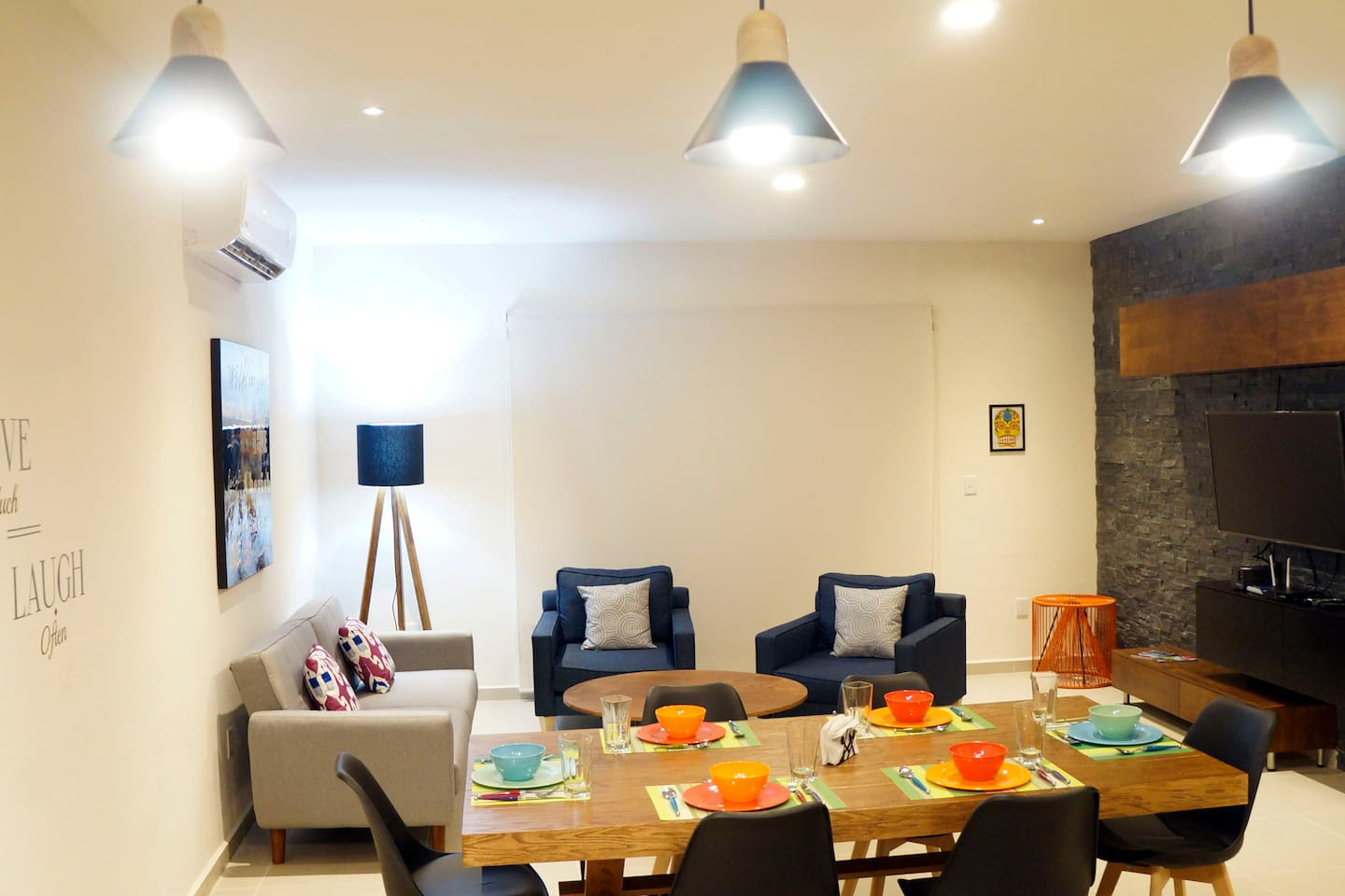Full equipped dining and living room with air conditioner, sofa bed, tv cable and balcony area with a pool view