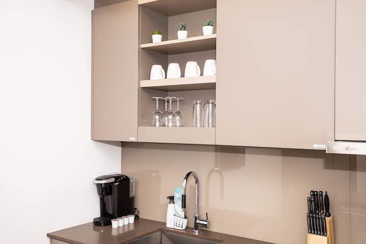 Fully stocked kitchen with drinking glasses, wine glasses, and coffee mugs.