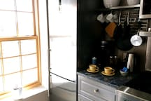 Our refrigerator and freezer is  tall and slim but has plenty of room for all your items. We provide you with a Brita water pitcher and Ice trays. The coffee station has Keurig , electric tea kettle and cups conveniently ready for you.