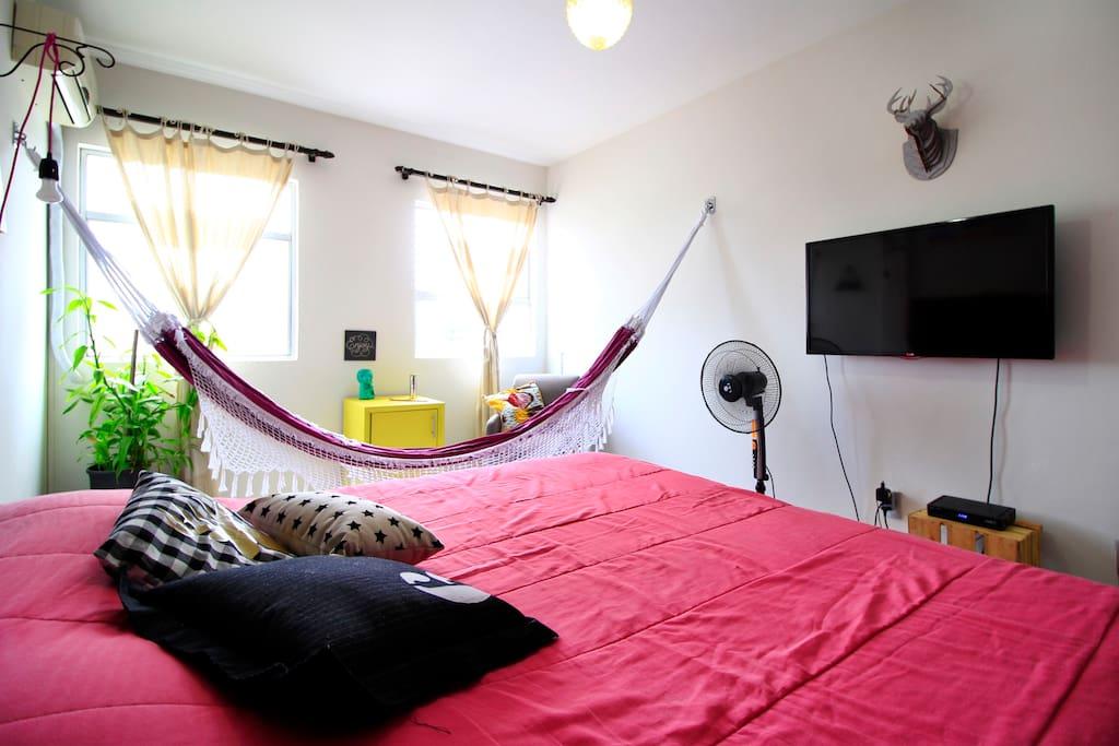 Suite de casal com cama king size, closet, TV e rede