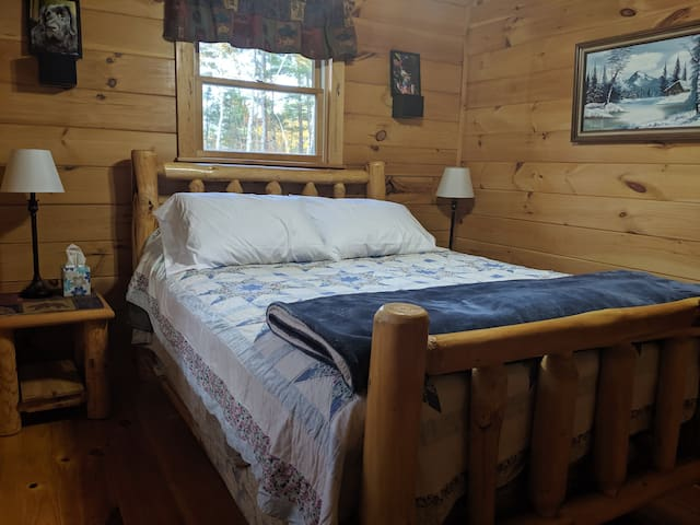 Warm and inviting bedroom with natural pine log bed and end tables