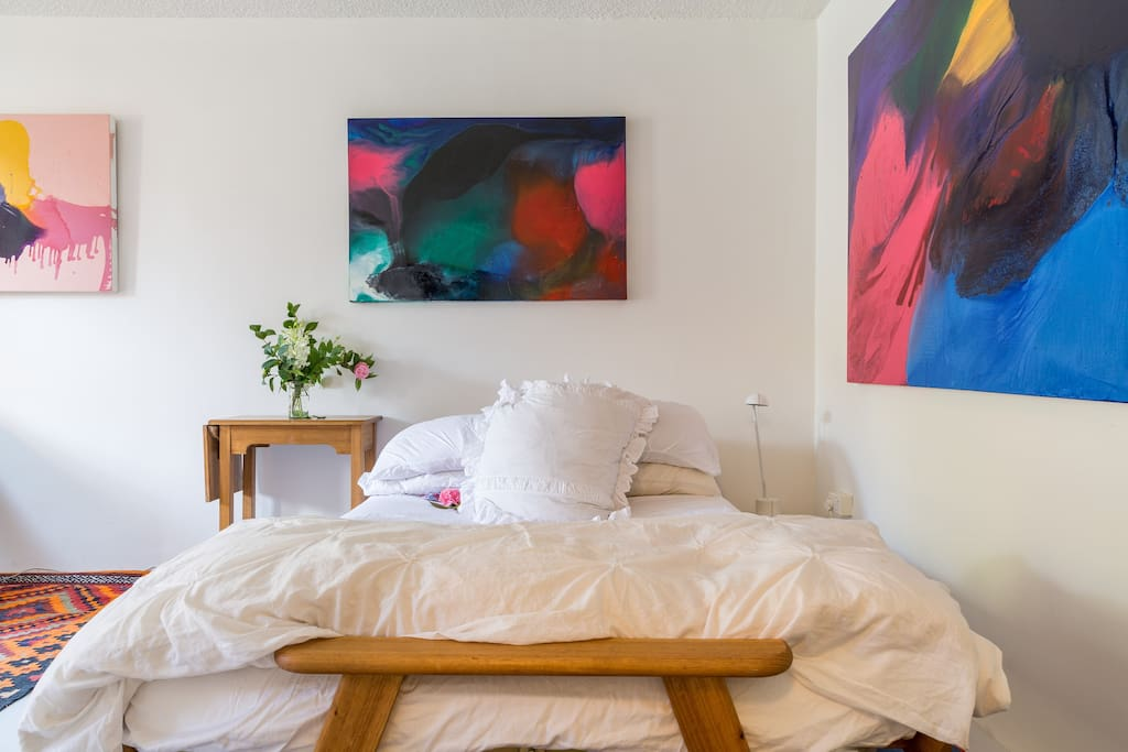 double bed with artworks by Michael Gray