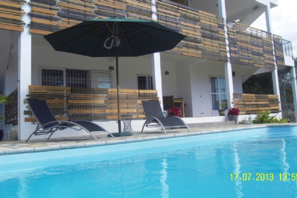 Transats, parasol au bord de la piscine pour un moment détente