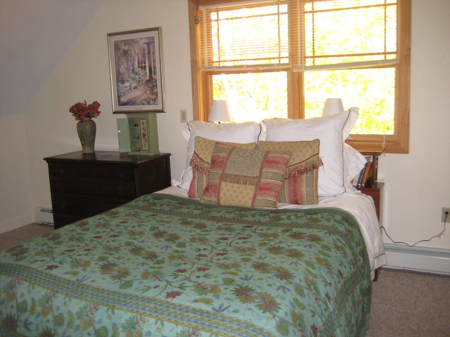 Large bedroom overlooks wooded area
