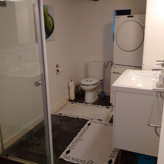 Badkamer met wasmachine en droger