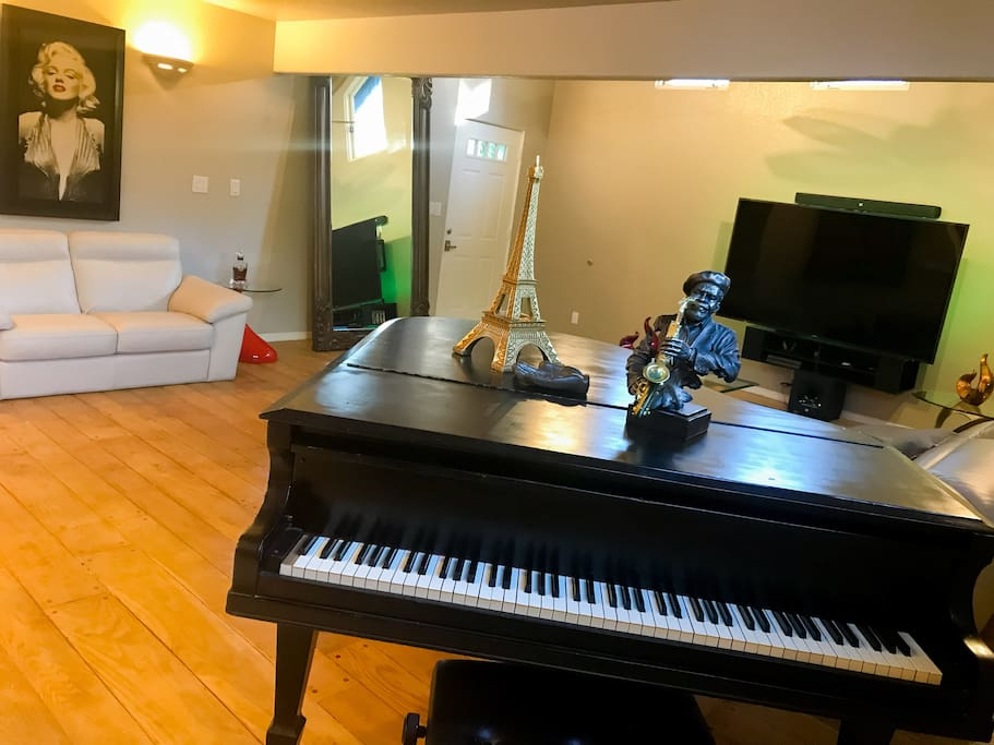 """Living room with piano and 75"""" tv."""