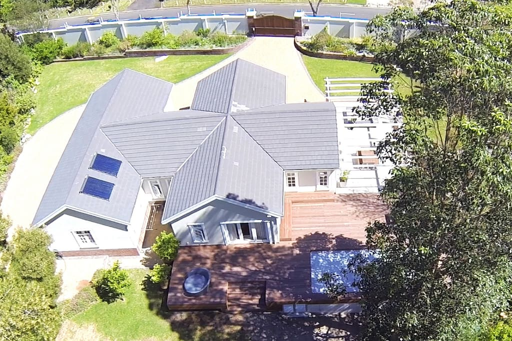 Drone aerial shot of the guest house with its private drive way, pool and deck