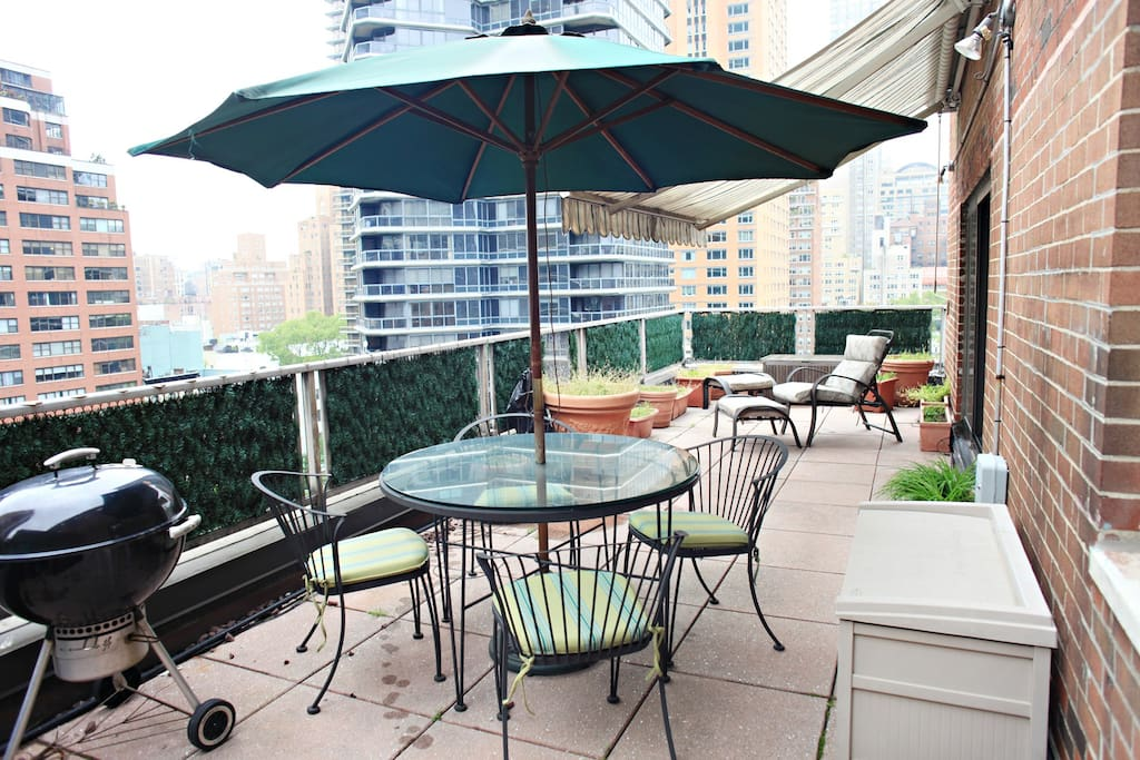 Terrace with charcoal grill, dining table with umbrella, roll out awning and lounge chair