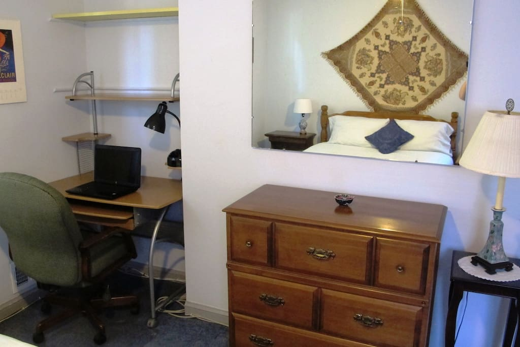 The room has a desk and chair, a chest of drawers, a large mirror, several lamps and side tables.