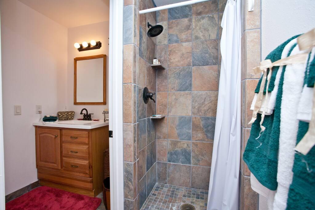 Big travertine shower with high-flow shower head