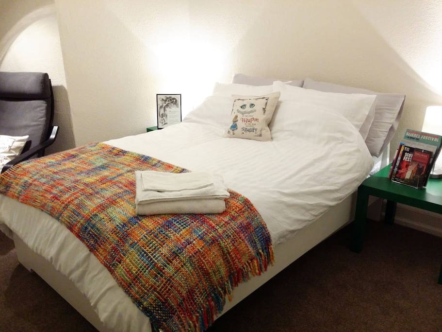 The bedroom: cozy and quiet with a large comfy double bed, new mattress, fluffy pillows, fresh pure cotton bedding, a comfy armchair to relax and enjoy the views and plenty of city and event guides for you to plan your adventures