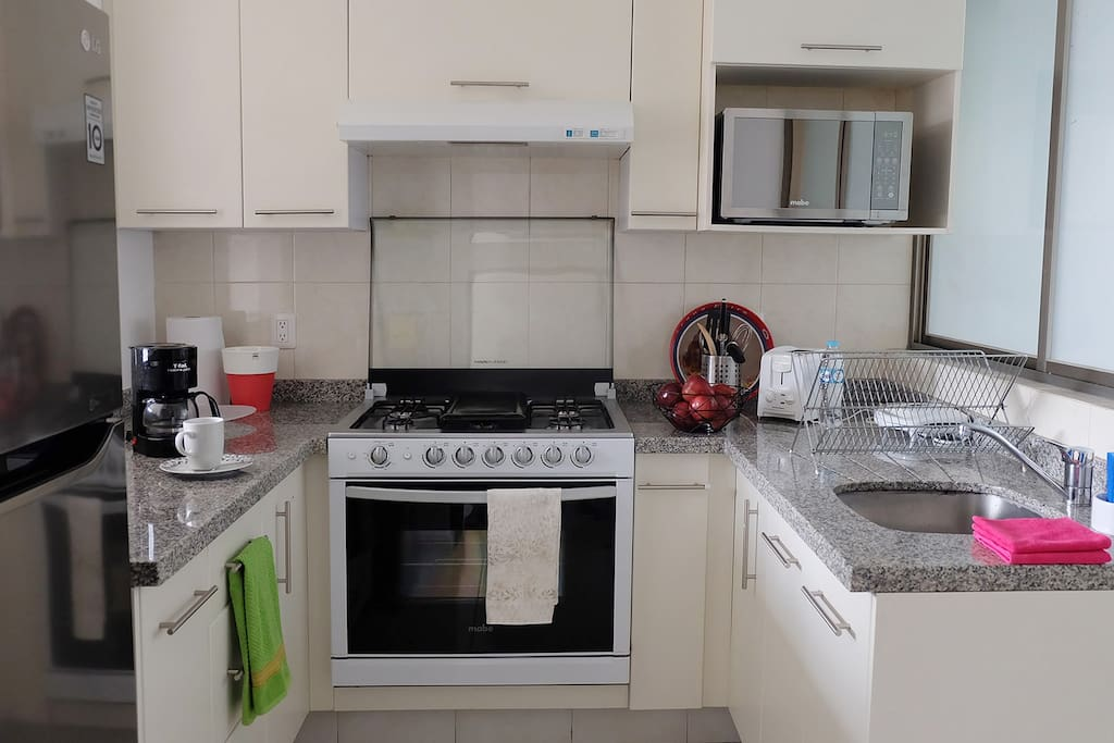 Full equipped kitchen with microwave, coffee maker, tea, dishes, utensils and toaster.