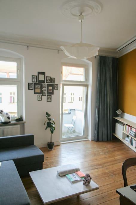 Wohnzimmer mit großer Couch und Tür zum Balkon