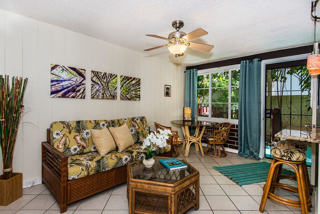Welcome to your garden condo with a vintage Hawaiiana theme. Recent updates include new custom cushions for the futon/sofa with slip covers of reproduction 1950s barkcloth, and room-darkening draperies. Bentwood rattan furnishings compliment the theme and provide additional seating.
