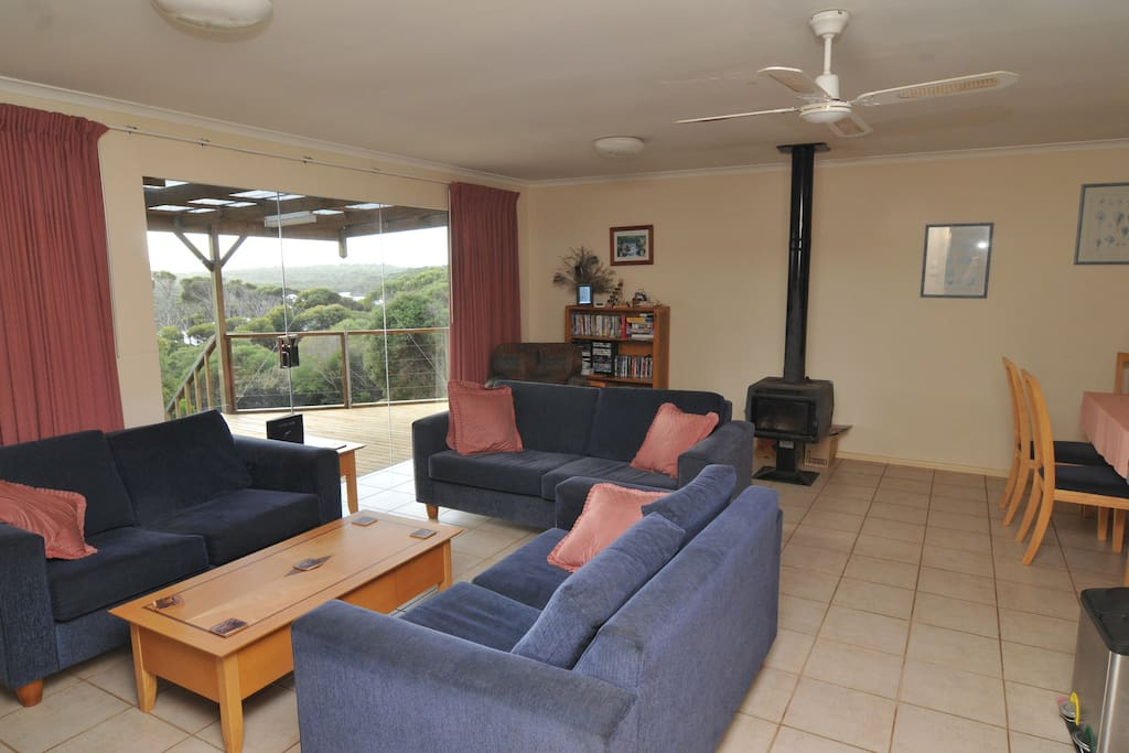 Large spacious living room with a fireplace. You can see the big windows to enjoy the beautiful views.