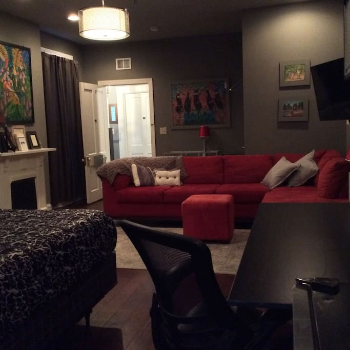 The room is spacious  with a comfy sectional sofa for napping, relaxing or enjoying the big screen TV