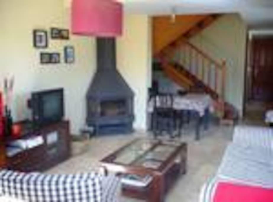 Salón de la casa, con chimenea y acceso a terraza