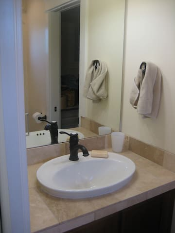 The sink, vanity and toilet (unseen) with window above toilet.