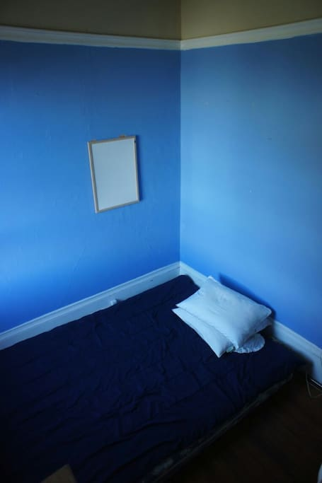 The colors of the room are blue and yellow. The room is well-lit from a window. There is a queen matress on the floe
