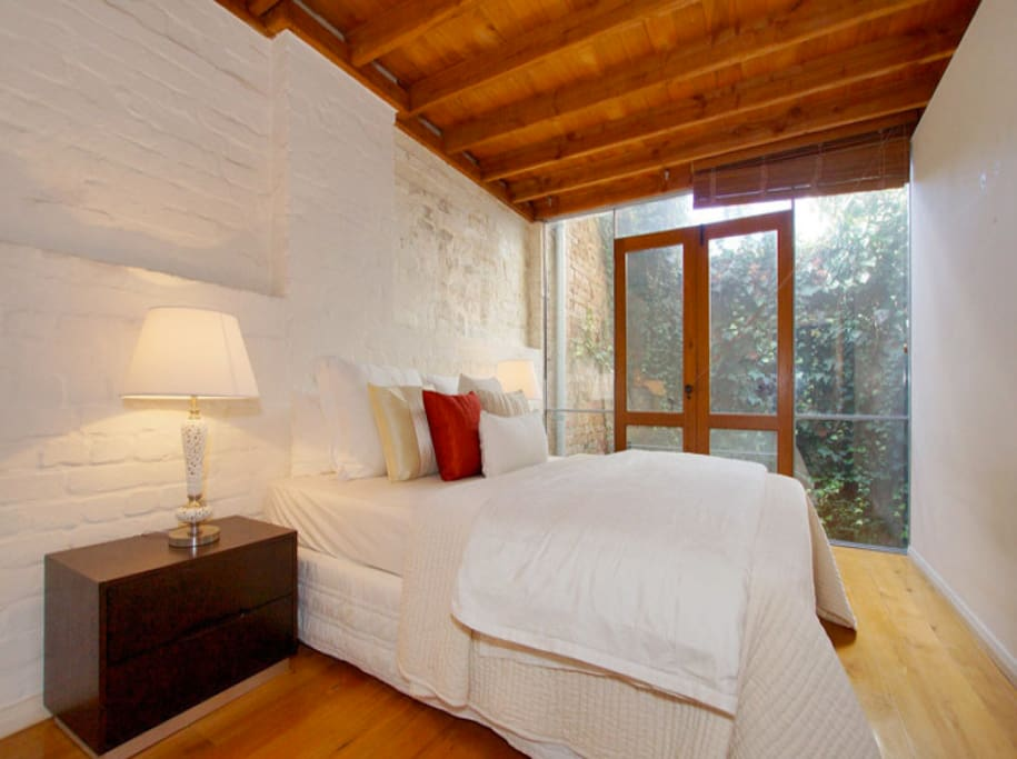 The first floor Queen bedroom overlooks the private ivy filled courtyard...