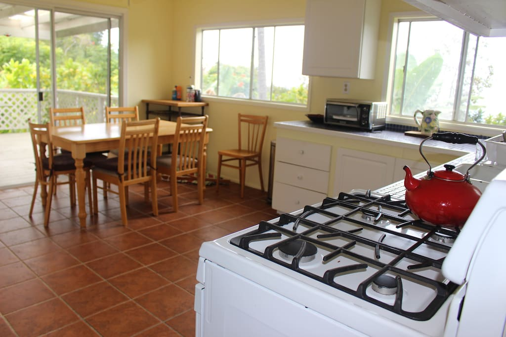Spacious kitchen with stove, toaster oven, refrigerator, and cooking and serving essentials.