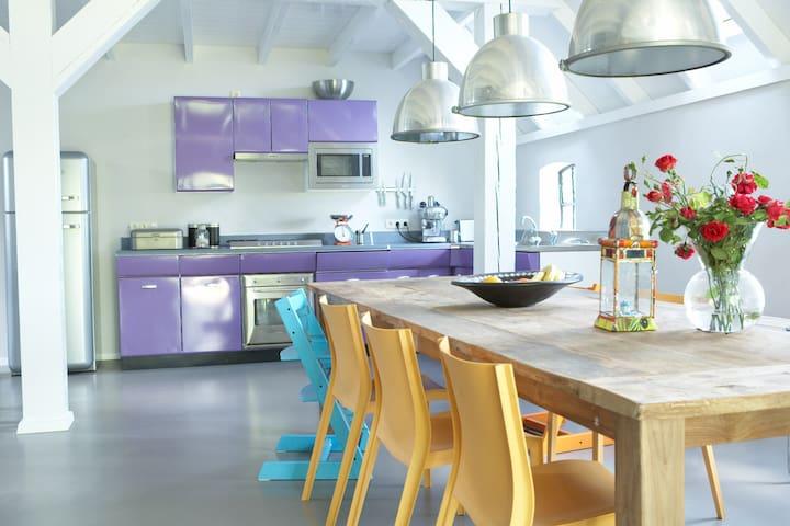 De modern ingerichte keuken met grote eettafel in de oude deel
