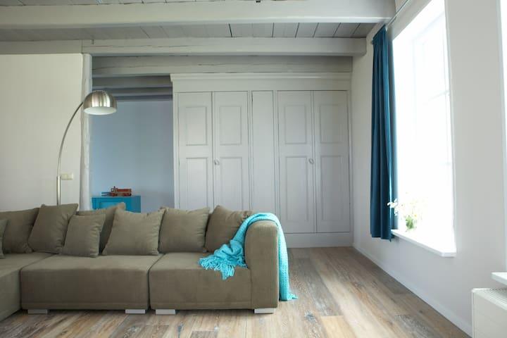 De voorkamer met de bank bij de houtkachel