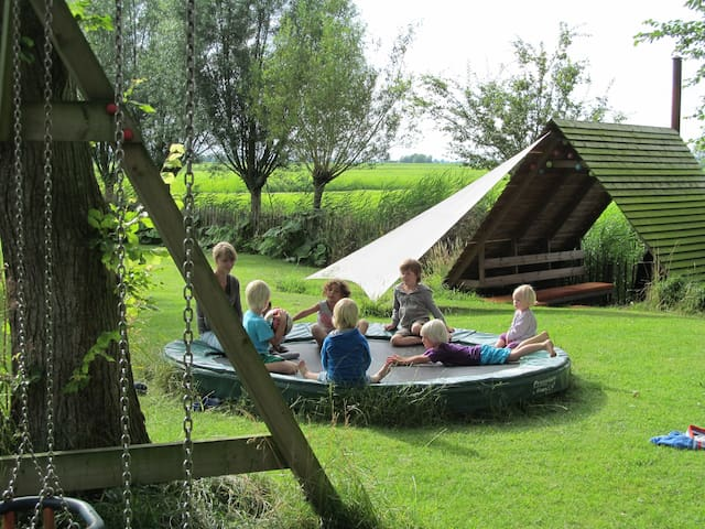 De speeltuin met trampoline en de overdekte vuurplaats