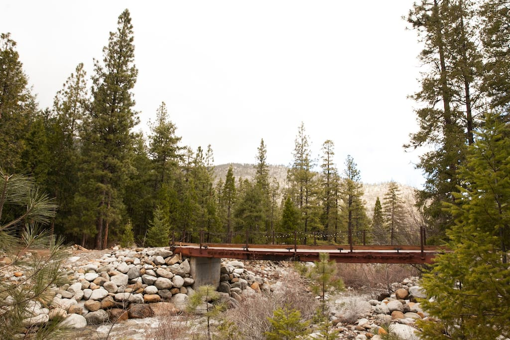 To get to the cabin, cross this sturdy bridge and then the cabin is just to your right along a dirt path as you follow the flowing creek.
