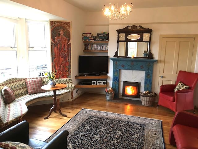 large lounge with window seats and woodburner