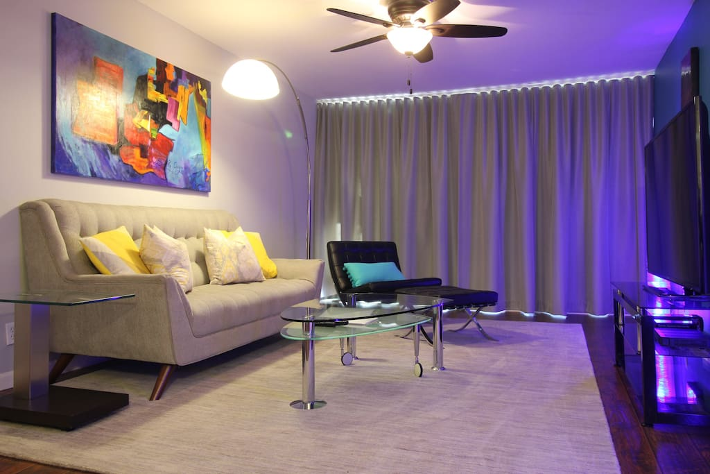 """Custom blackout drapes darken the living room if you'd like to take a nap or watch a movie on the 60"""" TV."""