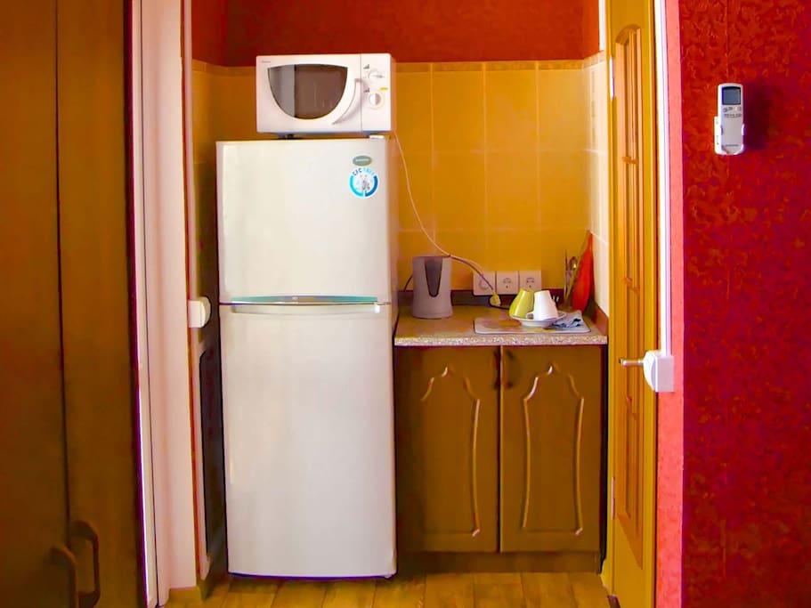 Здесь есть всё, что нужно паре или семье: тумбочка для посуды, электрический чайник, вместительный холодильник и микроволновая печь. А что ещё нужно для комфортного отдыха? А вот для приготовления пищи — удобная современная кухня со сплит-системой на перв