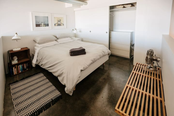 Upstairs bedroom features a queen sized bed with a firm organic latex mattress, 4 pillows, cotton sheets and duvet.  The washer+dryer, drying rack, dresser, hangers, mattress pad and additional towels + linens are located in the bedroom closet.