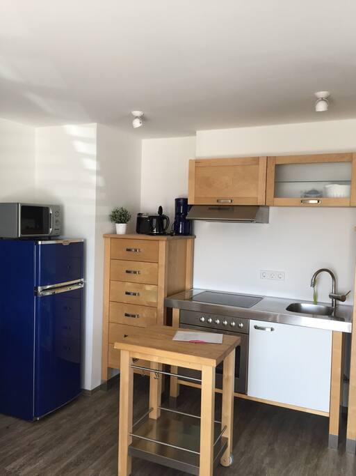 Die Küche mit Kühlschrank und Gefrierfach  (links), Mikrowellenherd, Kaffemaschine, Herd mit Backofen.