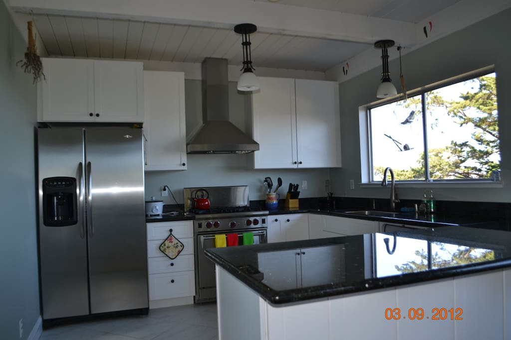 renovated kitchen with wolf range, granite countertops and stainless steel appliances