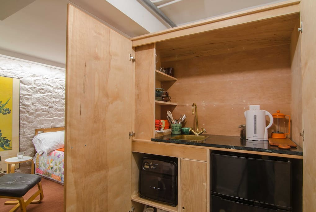 Kitchenette with fridge, microwave and sink.
