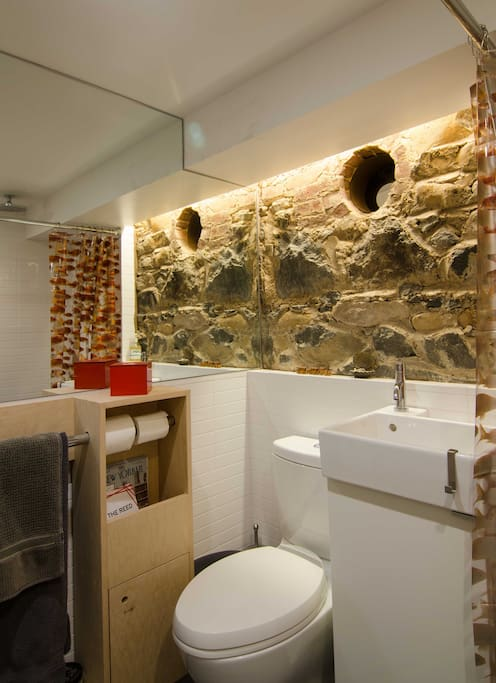 Bathroom featuring rain-shower and rock wall.