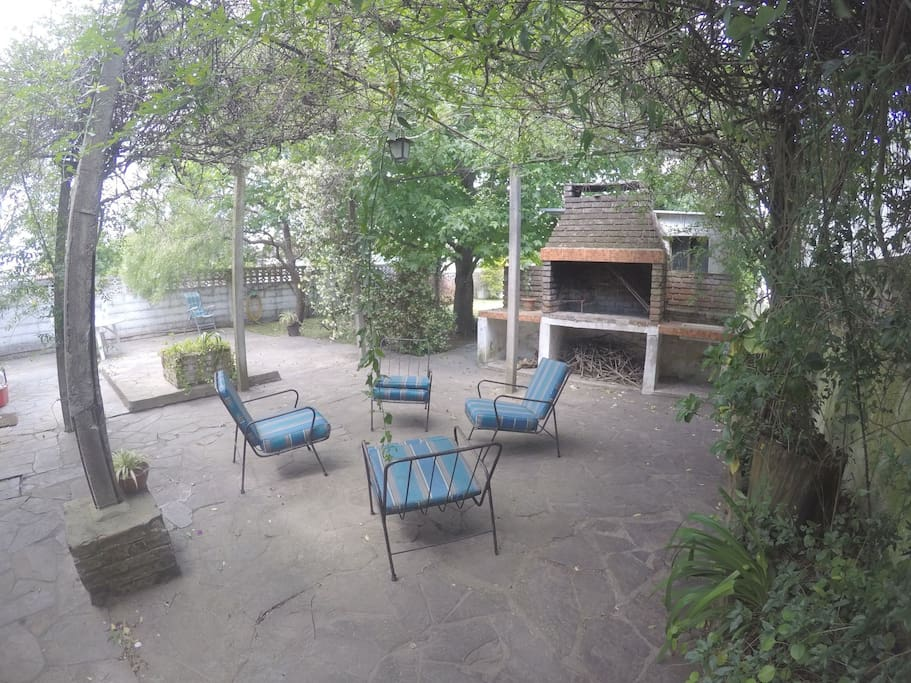 Zona de Barbacoa con amplio Parrillero juego de jardin para almorzar bajo los árboles y con vistas a un amplio jardin en el fondo  del chalet perimetrado