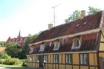 Taffeldækkerhuset as seen from the street with Tranekær castle in the background