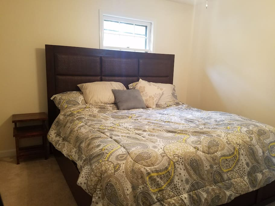 Cozy bedroom with king size bed, television, dresser and closet