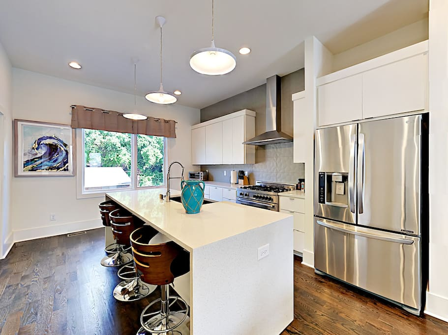 The kitchen island offers plenty of space for meal prep and doubles as a bar.