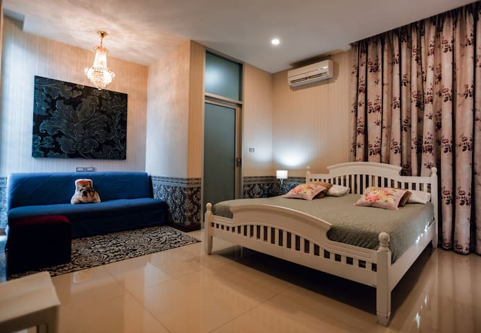 1st Floor. Bedroom 2. This room has to exit doors: one goes to backyard, another to Living room.  This room has kingsize wooden bed, sofa, aircond, lamp and private bathroom.