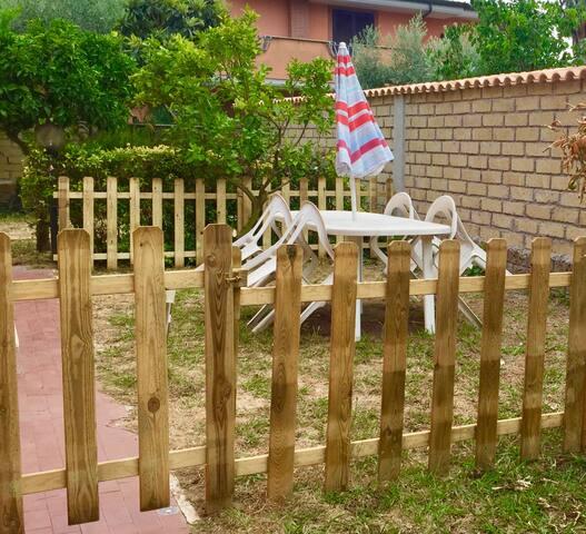 The fenced outdoor garden with wooden fence and the table - Il giardino esterno, recintato con steccato in legno