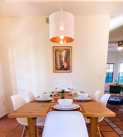 Dining table and chairs with contemporary Art and peek view into the breakfast room