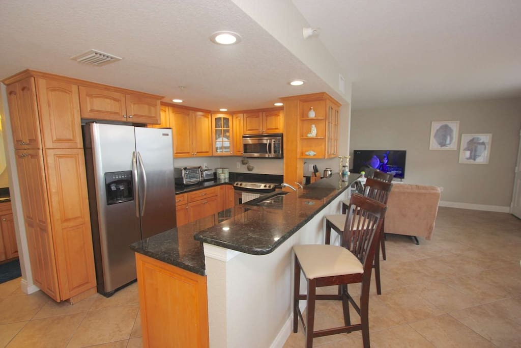 Entertain while packing a lunch for beach day or prepping a meal for the family in this beautifully updated kitchen with Granite Counter Tops and Stai