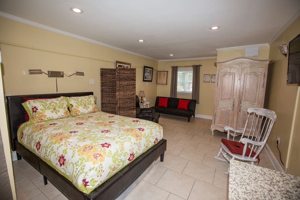 Queen size bed and comfortable living area.
