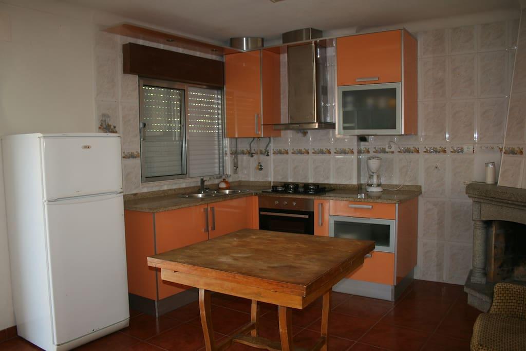 Leefkeuken met gasfornhuis, oven en koelkast/vriezer.
