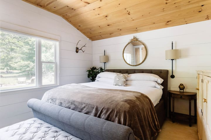 Country Master Suite With Wood Ceiling With a reclaimed wood ceiling and a tufted headboard, the master bedroom is the perfect mix of rustic and luxurious. A large picture window fills the space with light and showcases views of the garden.