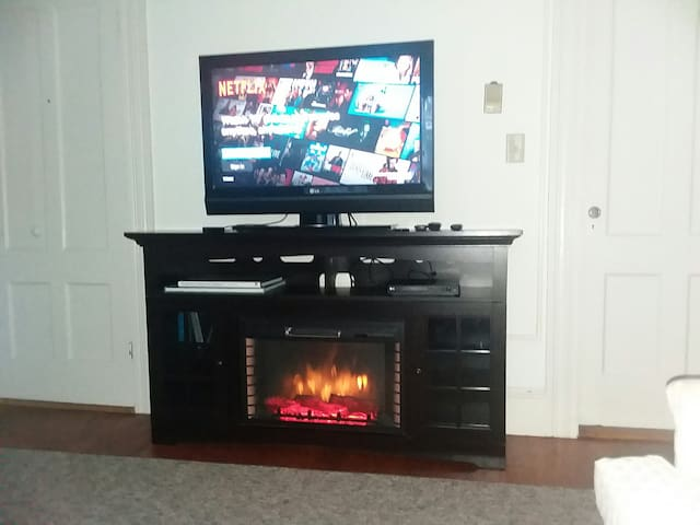 Ambiance is added to the living room with an electric fireplace that can be operated with or without heat. The television screen is connected to a roku device.